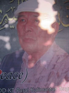 Prof. Haji Kena Muhamad Aini, MA bin Matseman Usop, dalam, potret cat minyak. Lahir di Balawang, Kuala Kapuas, 5 Juli 1936, meninggal di RSU Dr. Syaiful Anwar Malang pada 16 Agustus 2015  pukul 06.10 WIB. Dikebumikan di pemakaman umum Km.12 Palangka Raya pada 17 Agustus 2015. Seorang pemuka masyarakat Dayak Kalimantan Tengah telah pergi selamanya. (Foto. Dok. Lembaga Kebudayaan Dayak Kalimantan Tengah/Andriani S. Kusni, 2015).